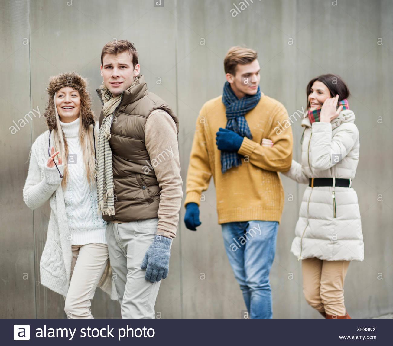Sorridente coppie giovani a piedi contro la parete Immagini Stock