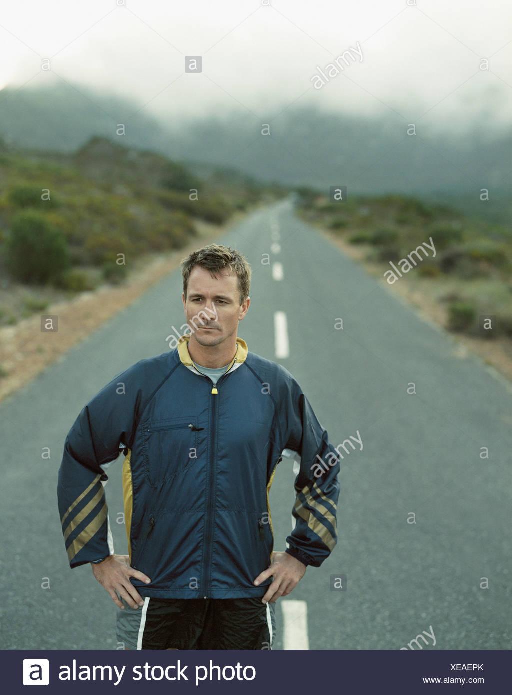 Un stoico uomo in piedi su una strada desolata Immagini Stock