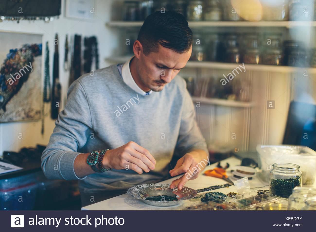 Un uomo che fa gioielli di perline Foto Stock