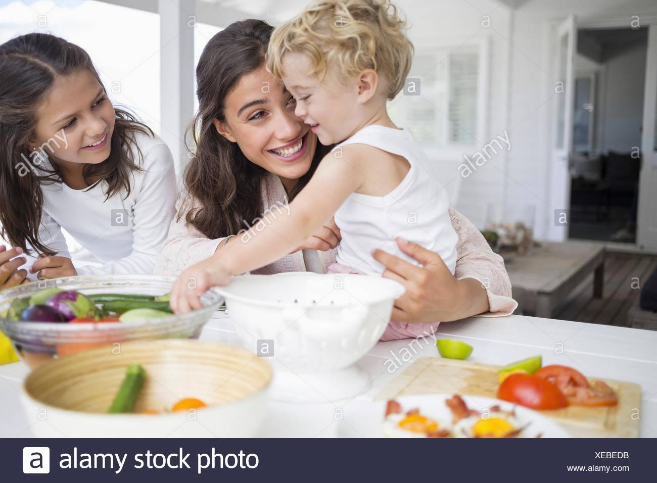 Felice famiglia giovane preparare verdura a casa Foto Stock