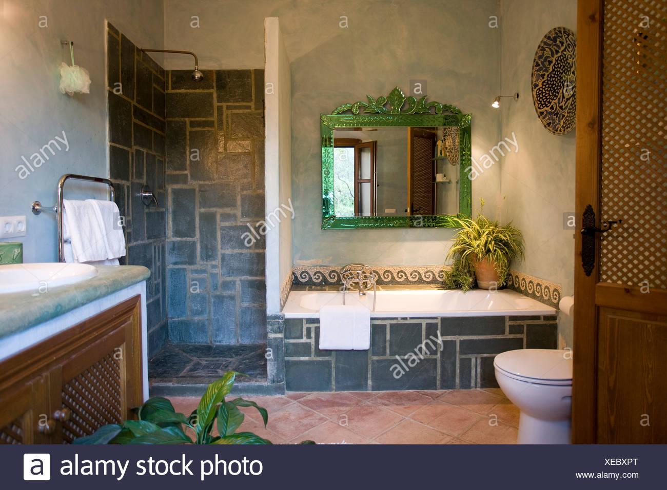 Green specchio incorniciato sopra con bagno in piastrelle di ardesia