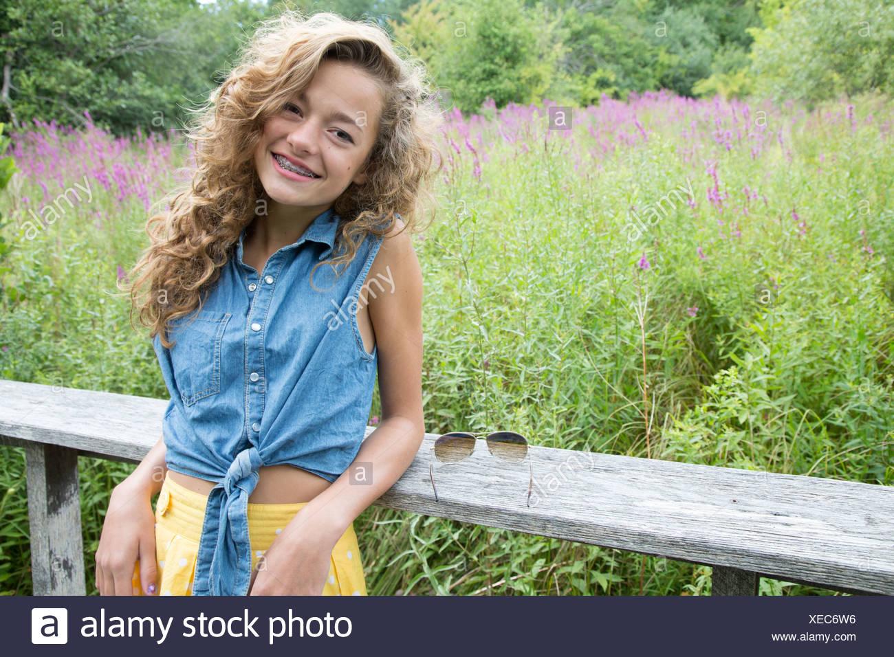 Ritratto di ragazza adolescente appoggiata sulla recinzione di legno Foto Stock