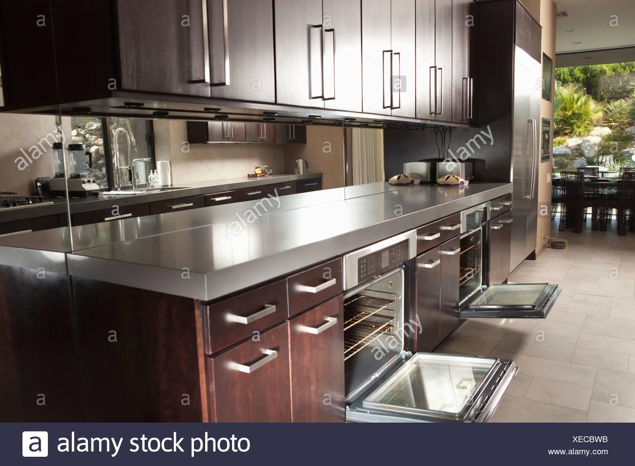 Legno scuro Isola per cucina con forno aperto le porte Foto ...