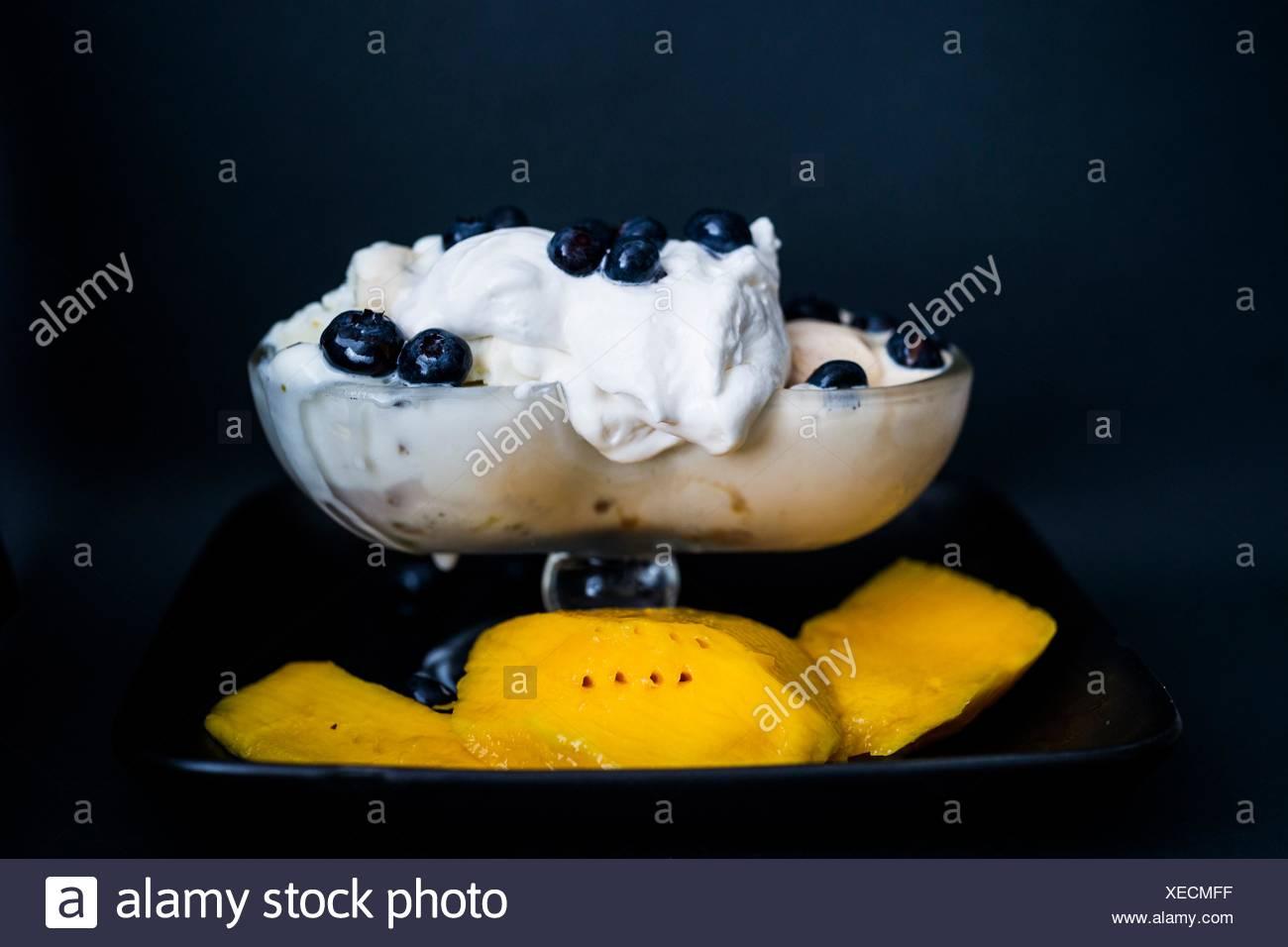 Dolce indulgenza. Gelato alla crema con panna montata, mango e mirtilli. Foto Stock