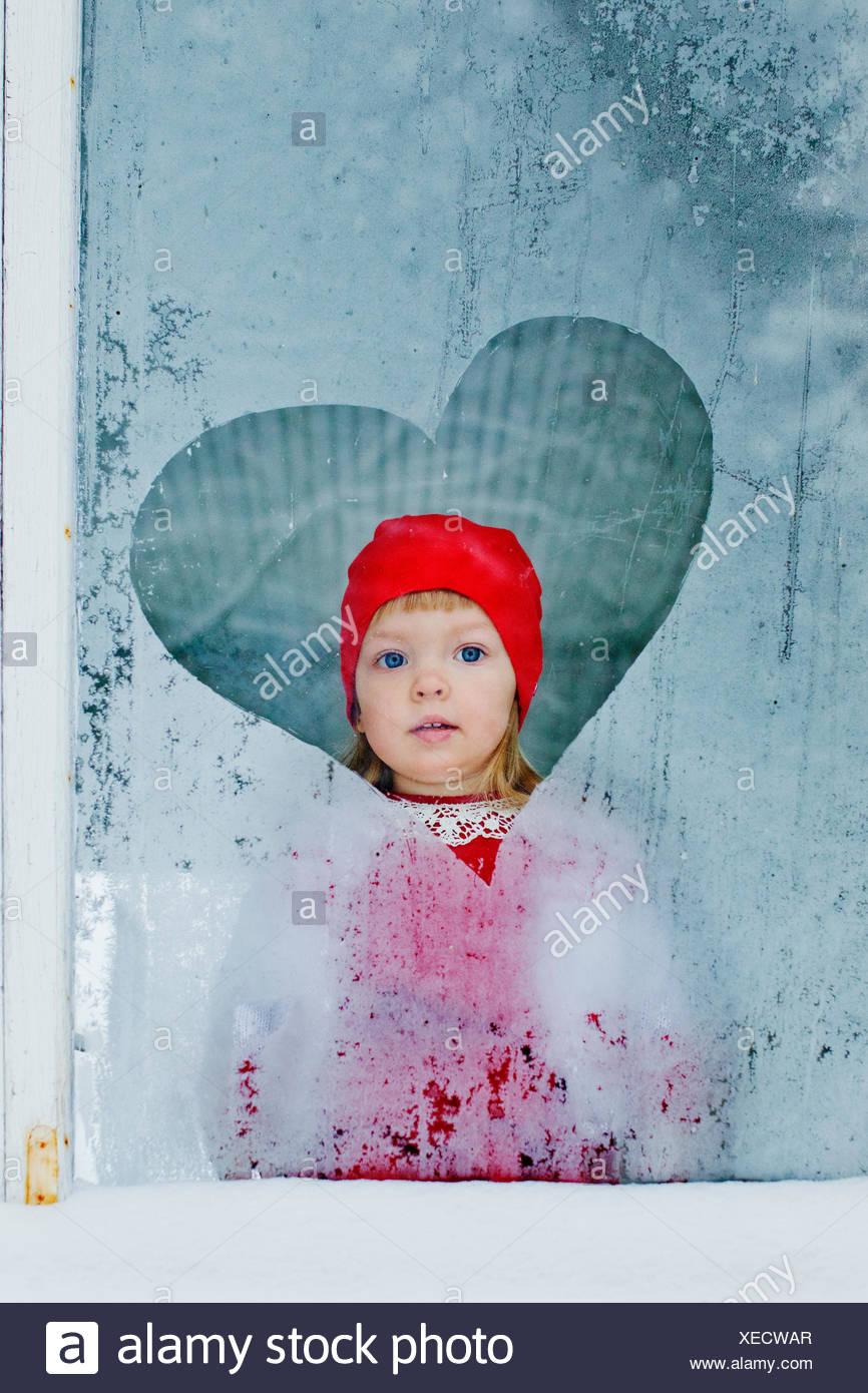 Ritratto di ragazza (4-5) guardando attraverso la finestra congelati Immagini Stock