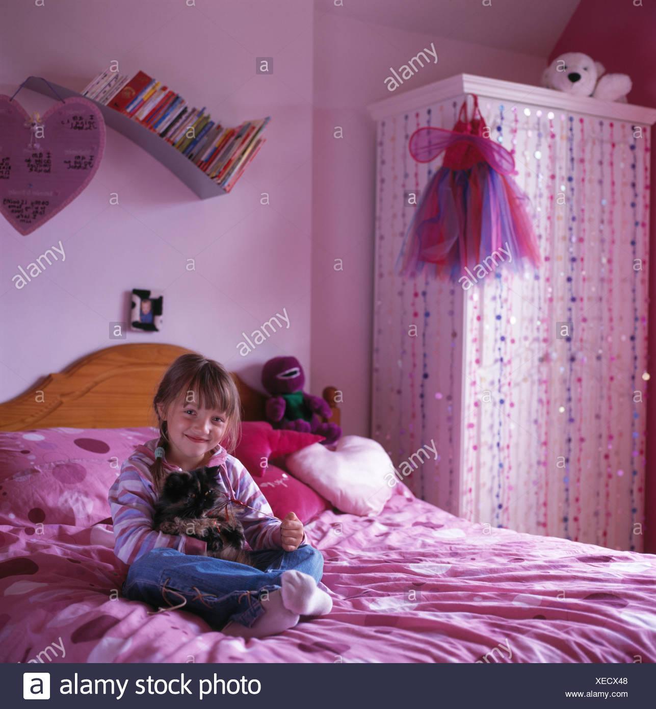 Piccola ragazza seduta sul letto nel bambino degli anni novanta rosa ...