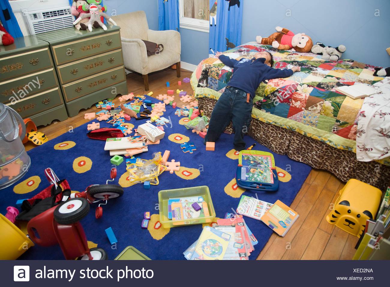 Ragazzo asiatico in camera da letto disordinato Immagini Stock