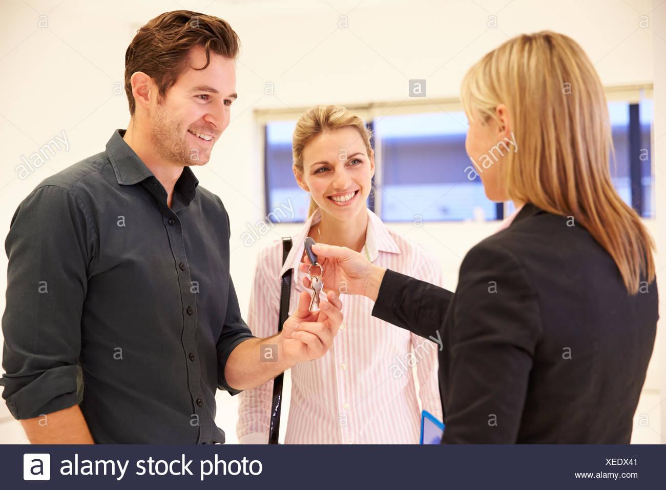 Agente immobiliare di consegnare le chiavi di spazio in ufficio Immagini Stock