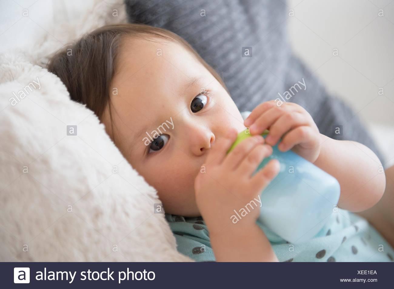 Ritratto di bambino sul divano a bere dal baby cup Immagini Stock