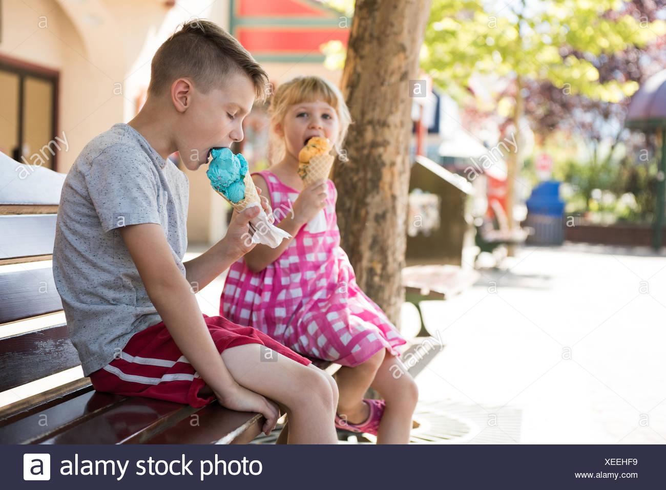 I gemelli a mangiare il gelato sul banco di lavoro Immagini Stock