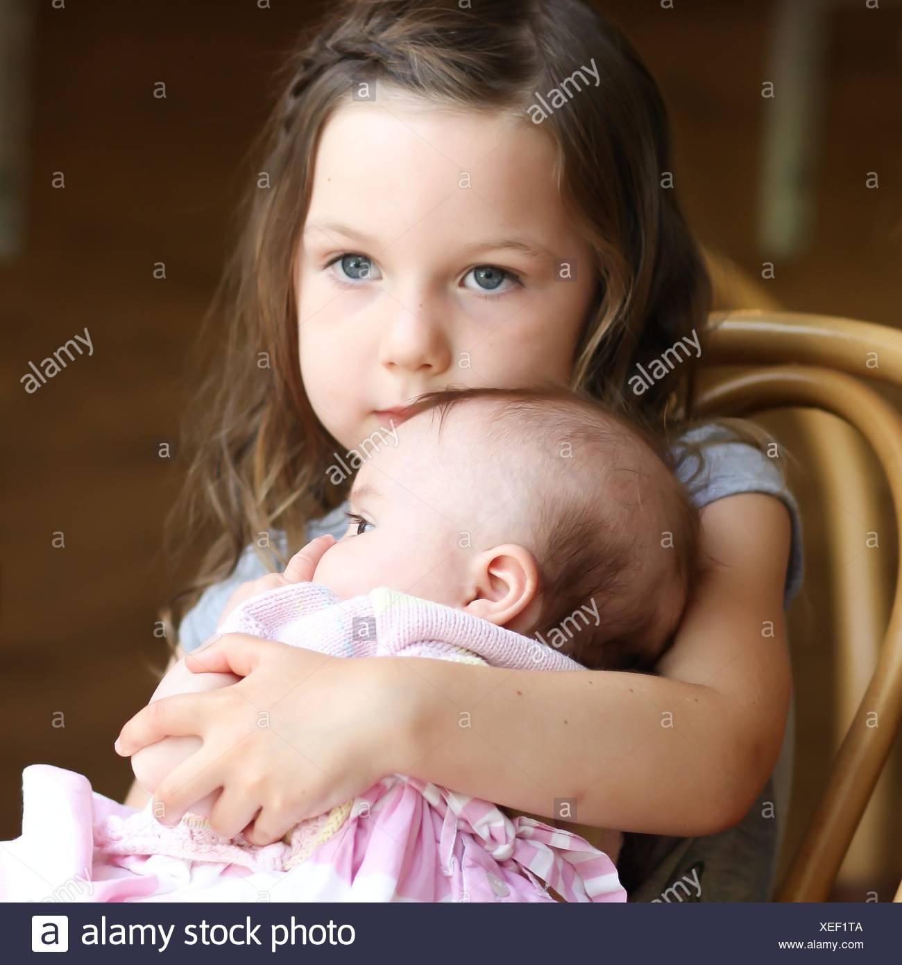La ragazza (4-5 anni) cuddling baby sorella Foto Stock