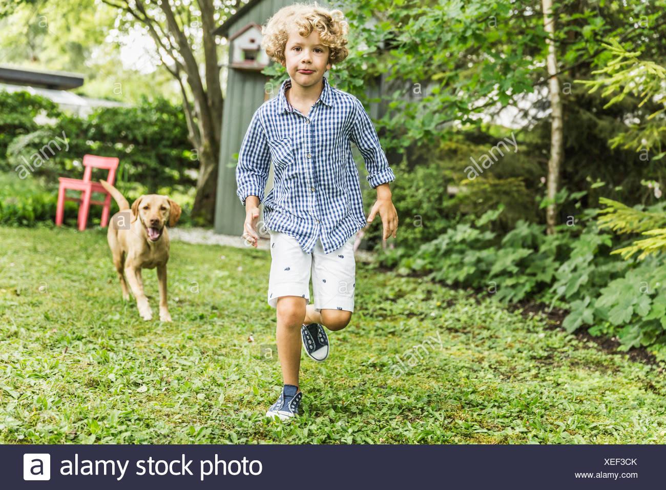Ragazzo in esecuzione con il cane in giardino Immagini Stock