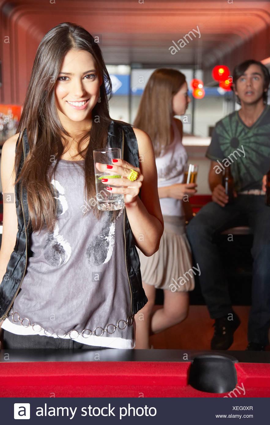Donna con la bevanda da tavolo da biliardo sorridente Immagini Stock