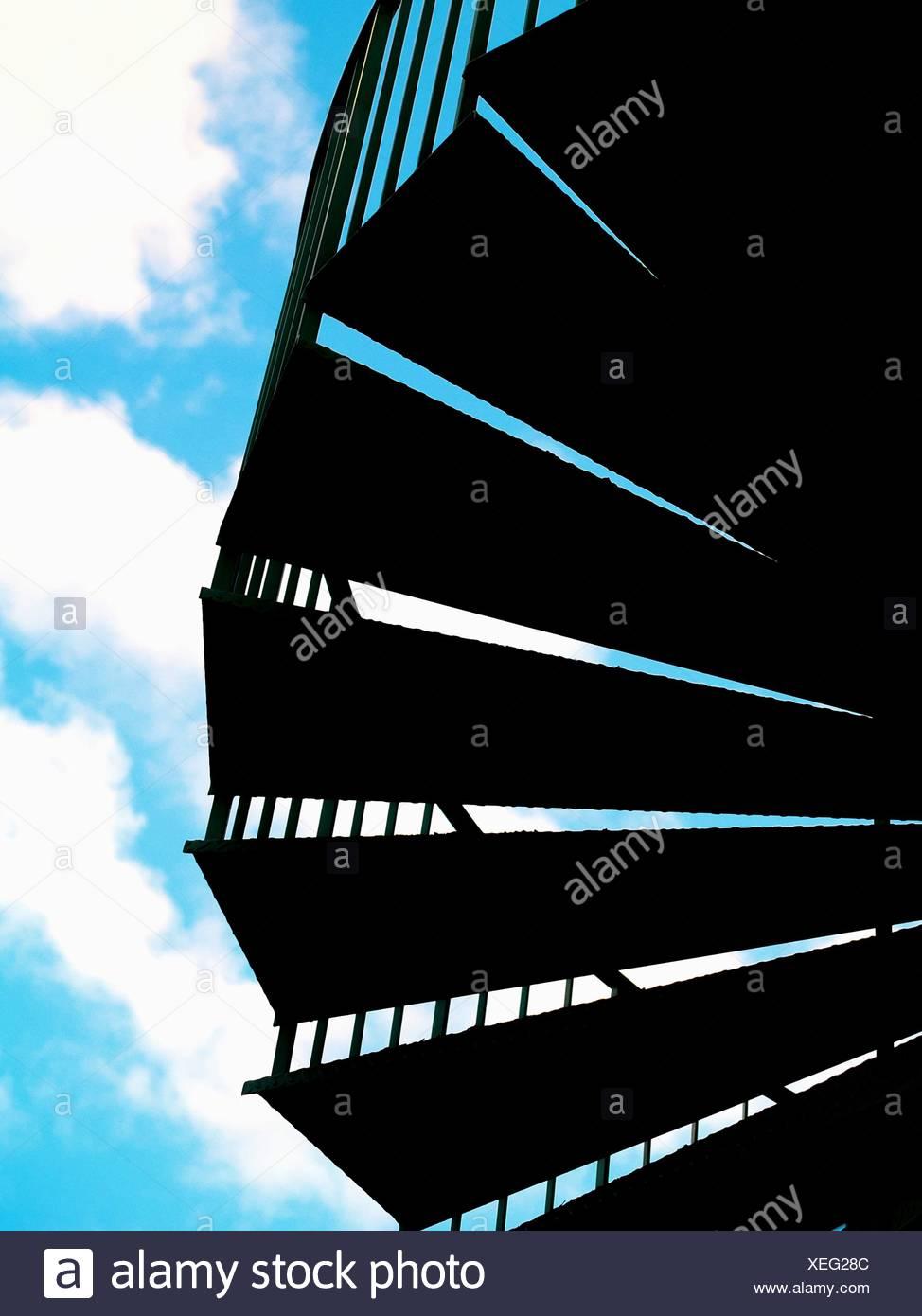 Basso angolo vista di Silhouette passi contro il cielo nuvoloso Immagini Stock