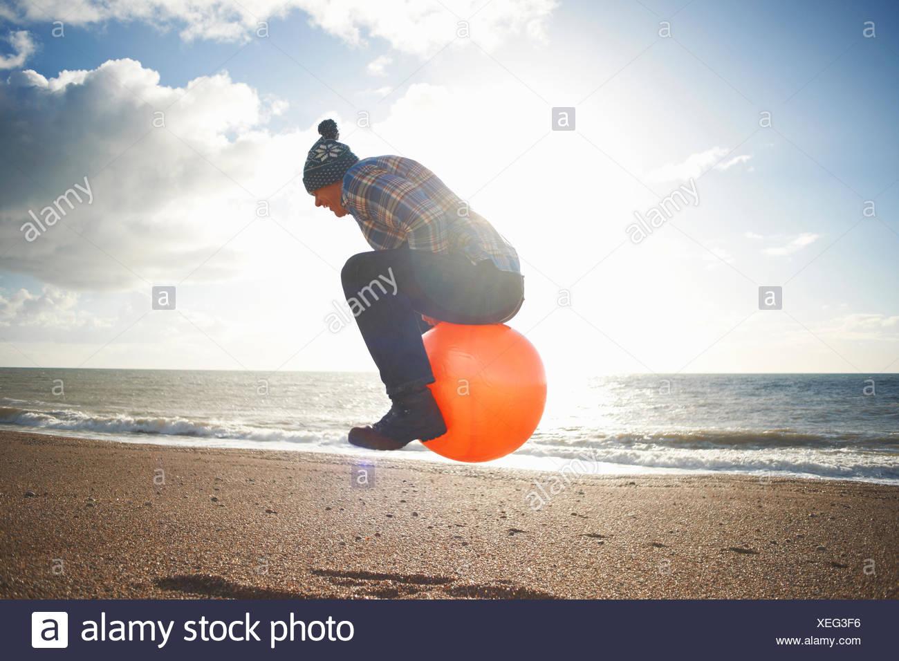 Uomo maturo jumping metà aria sulla tramoggia gonfiabile in spiaggia Immagini Stock