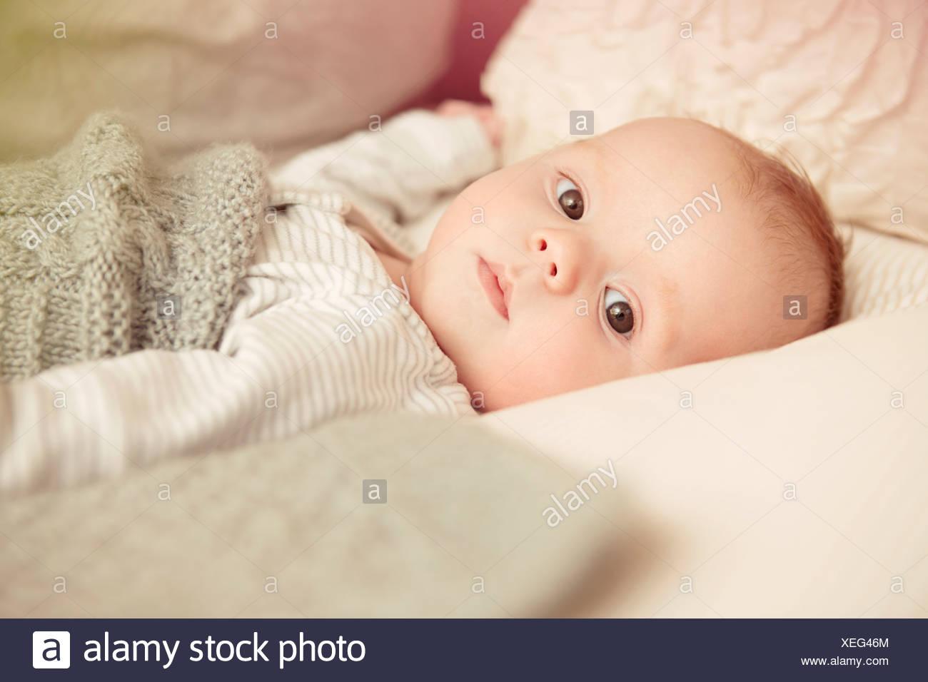 Di due mesi di età Bimbo giacente svegli nel presepe Immagini Stock