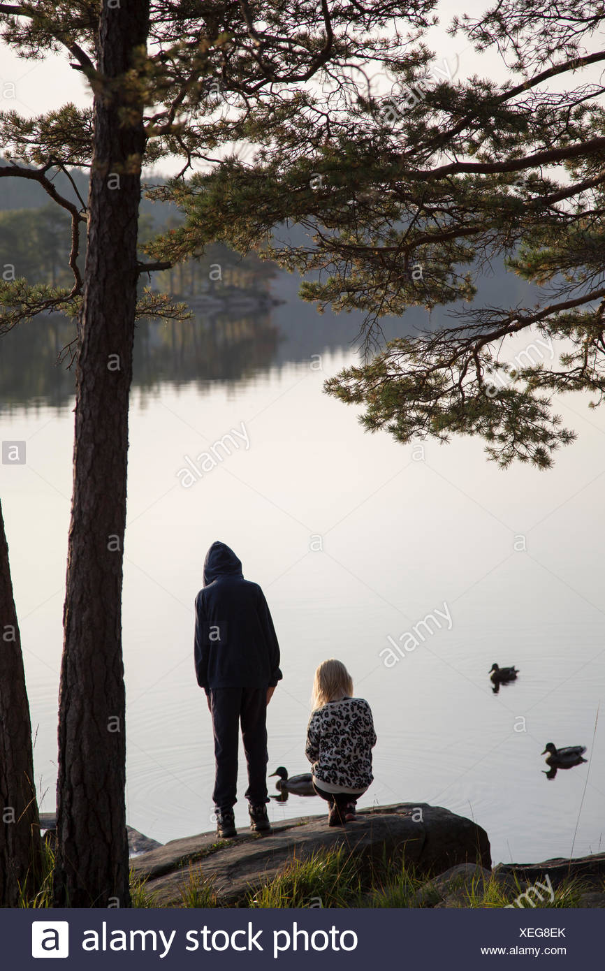 La Svezia, Vastergotland, Harskogen, Stora Harsjon, ragazzo (12-13) e la ragazza (10-11) dal lago Immagini Stock
