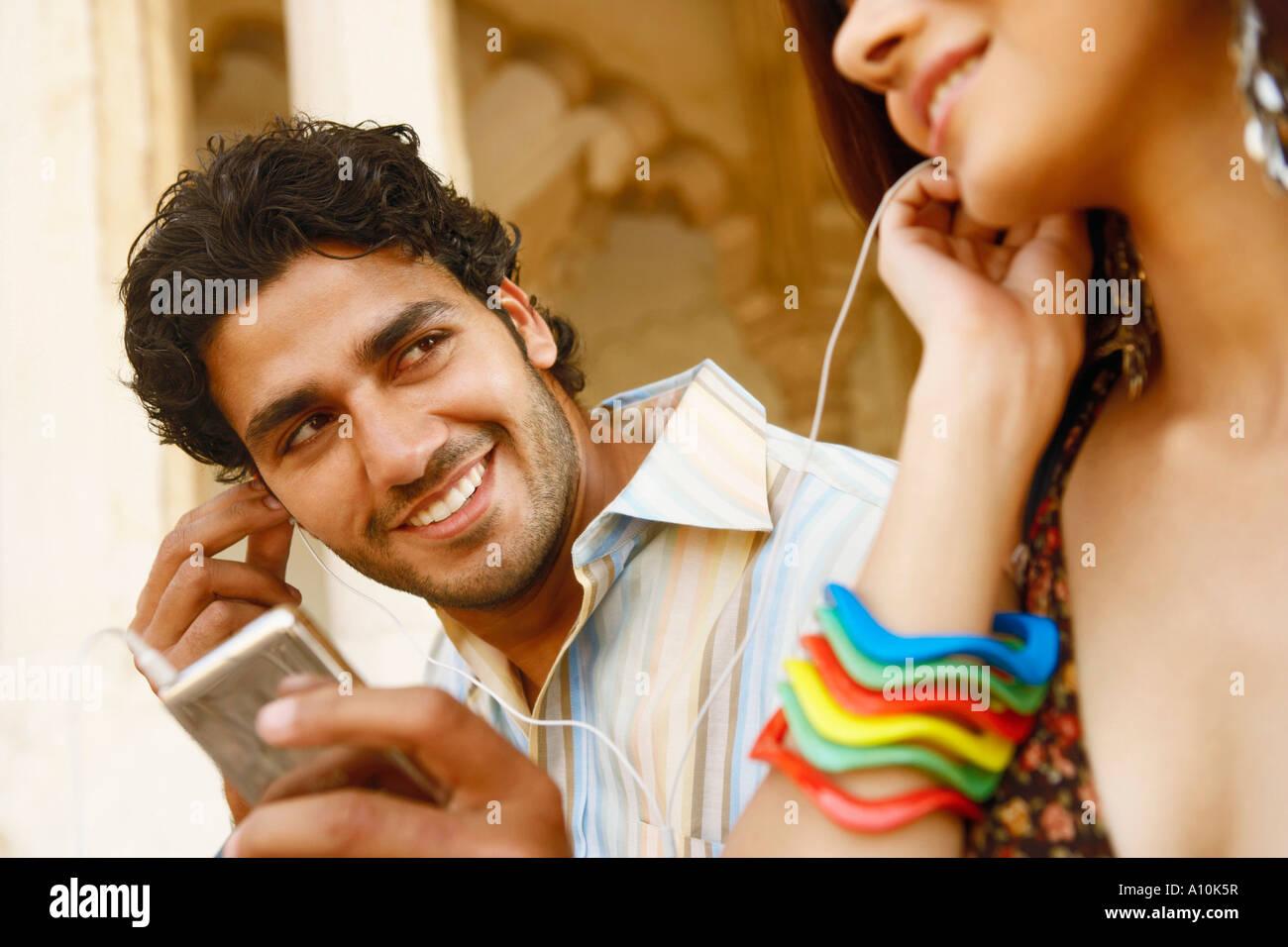 Close-up de um jovem casal para ouvir música em fones de ouvido, Agra Fort, Agra, Uttar Pradesh, Índia Imagens de Stock