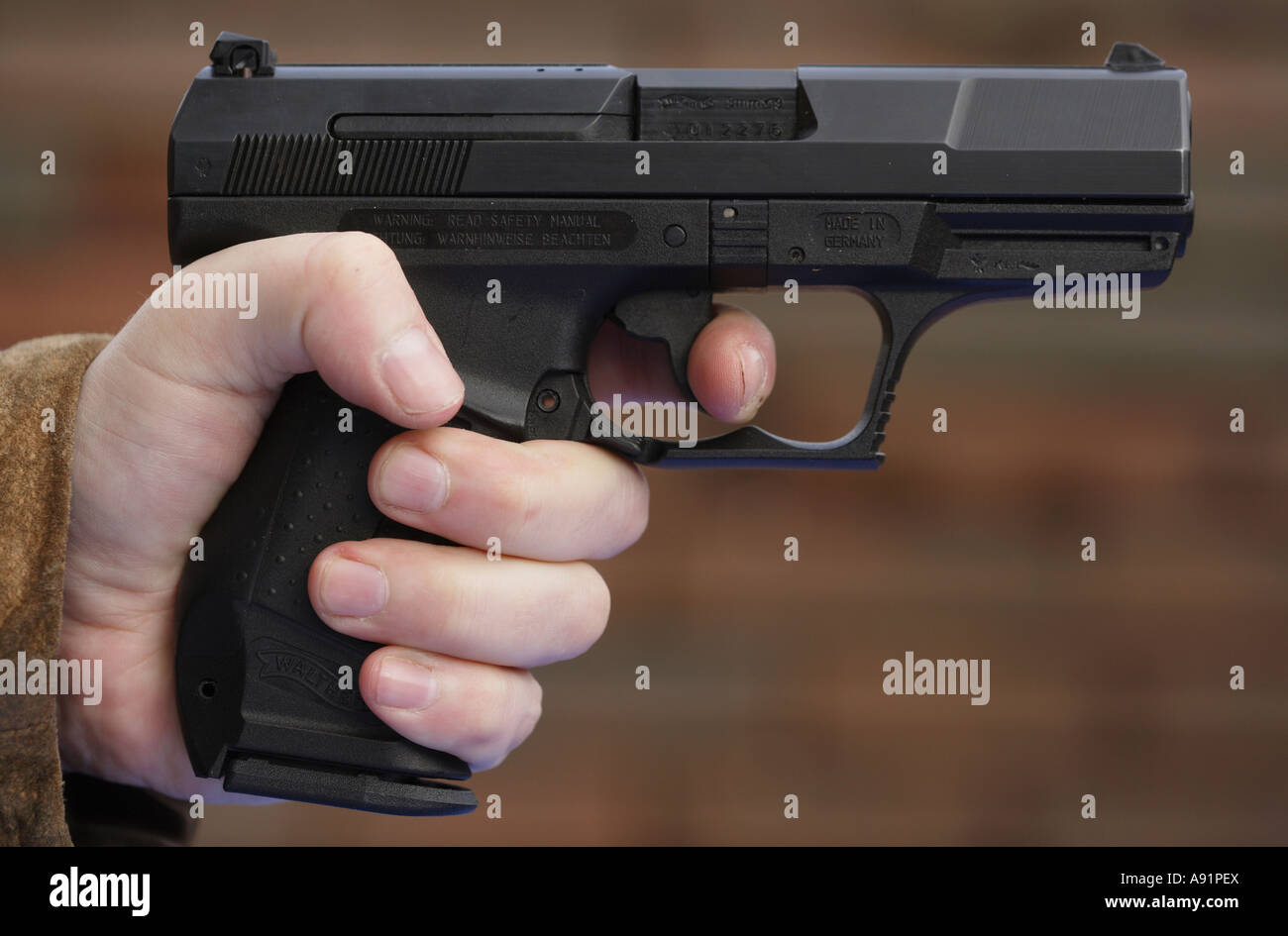Finger at the trigger of a pistol Walther P99 Stock Photo