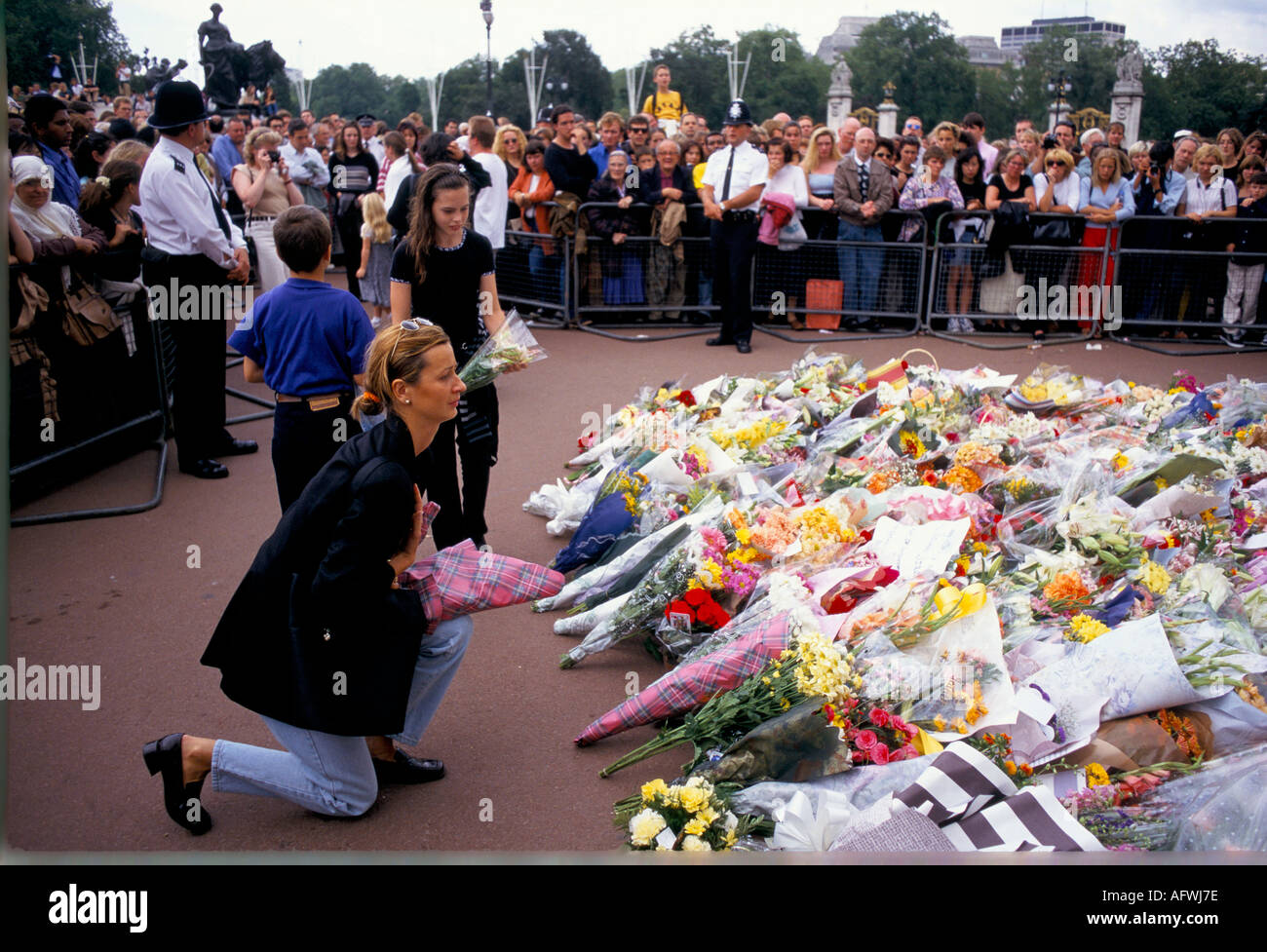 Mulher ajoelhada enquanto estabelece FLORES PARA DIANA em Buckingham Palace Londres 1997 Imagens de Stock