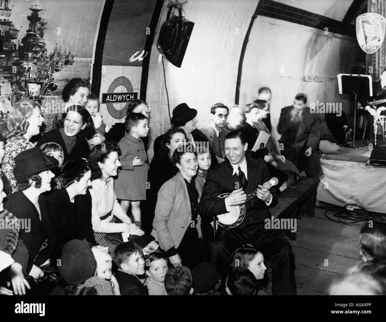 GEORGE FORMBY UK music-hall artista entretém os londrinos abrigadas do alemão bombardeios na estação de metro de Foto de Stock