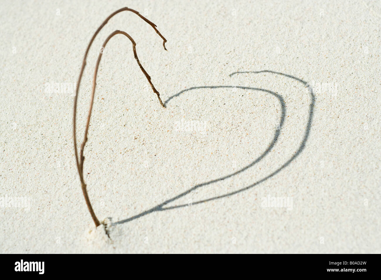 Ramos e sombras dispostos em formato de coração na praia, close-up Imagens de Stock
