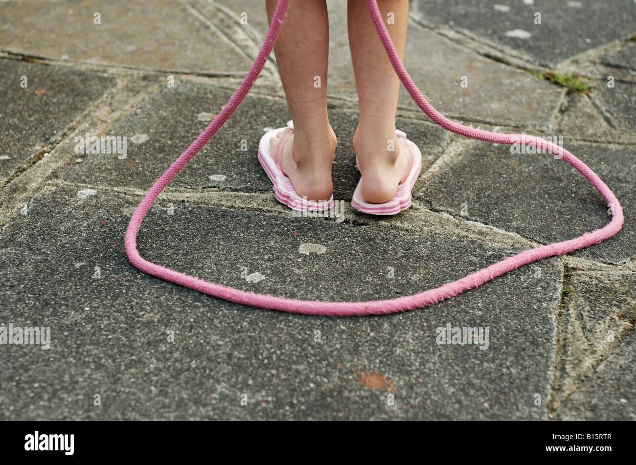 Criança com rosa pulando corda Imagens de Stock
