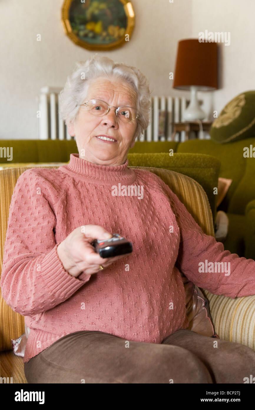 Em ihren Frau Siebzigern sitzt im Sessel im Wohnzimmer mit einer Fernbedienung Imagens de Stock