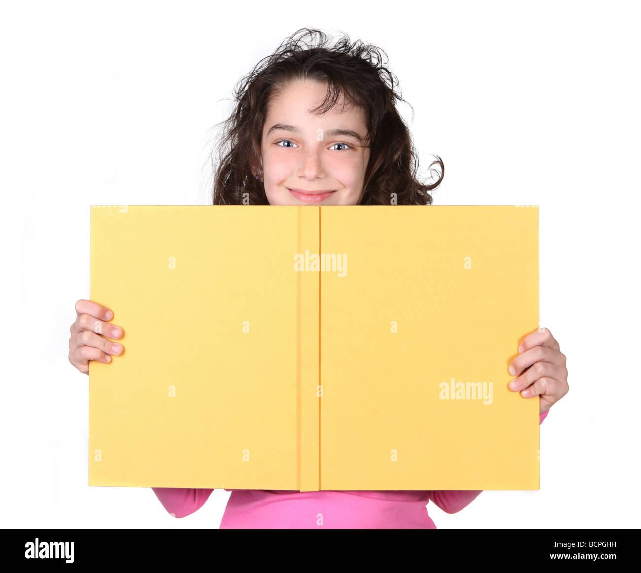 Rapariga a olhar por cima do seu livro escolar com um sorriso sobre fundo branco Imagens de Stock