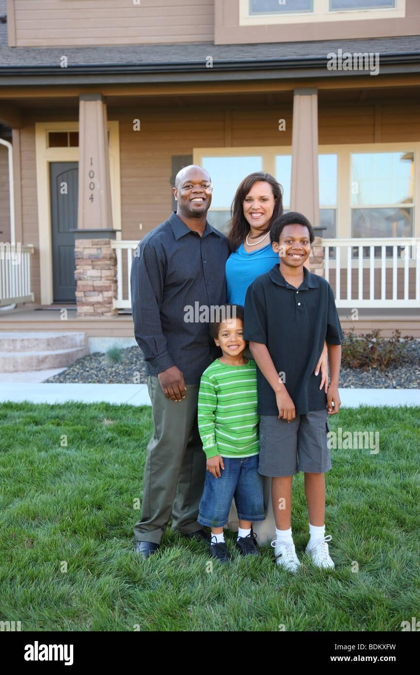 Família em frente da casa Imagens de Stock