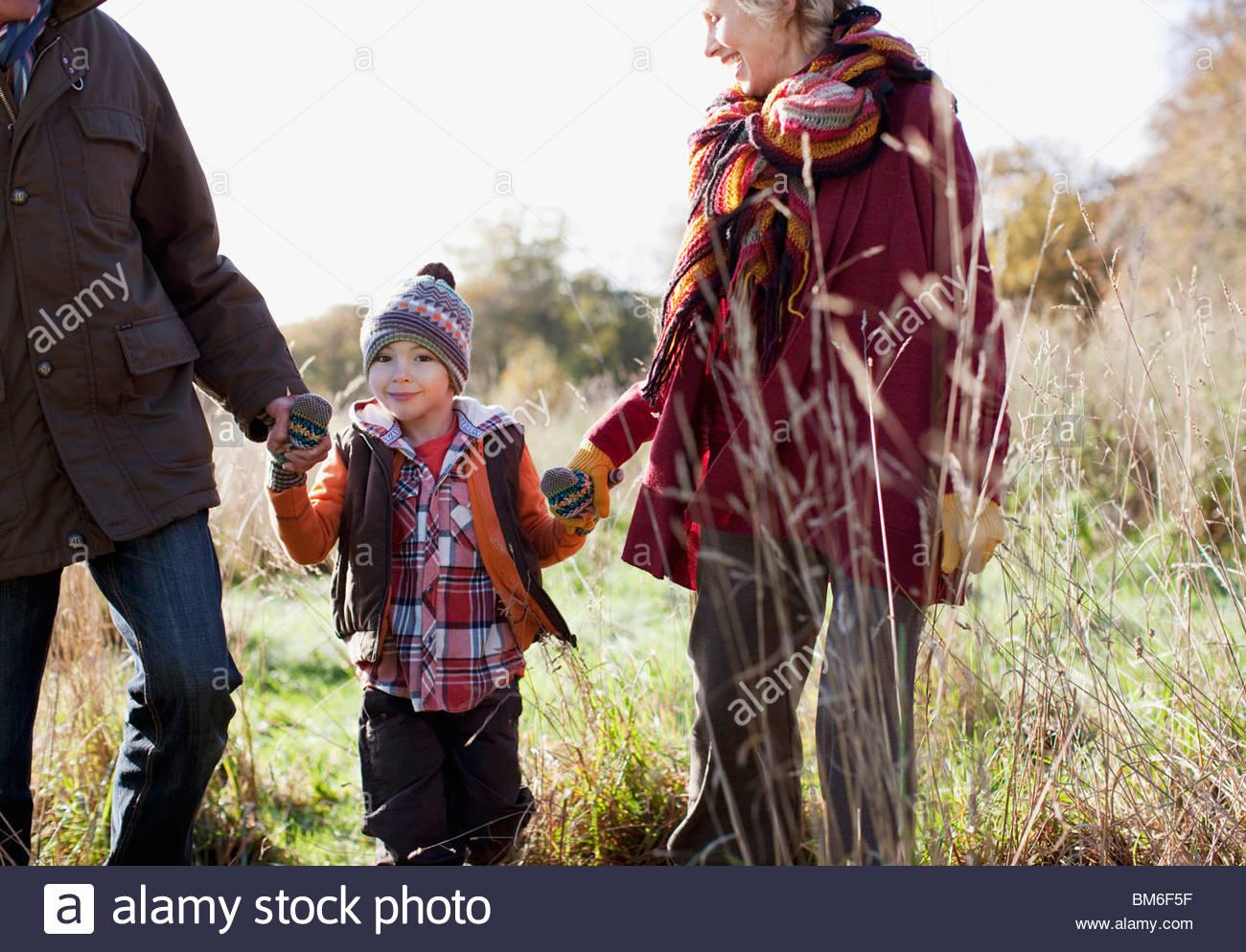 Avós segurando as mãos com o neto no exterior Imagens de Stock