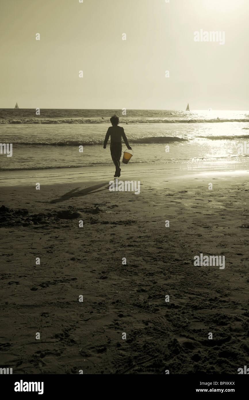 Sépia imagem do menino a trabalhar na praia com caçamba perto do oceano Imagens de Stock