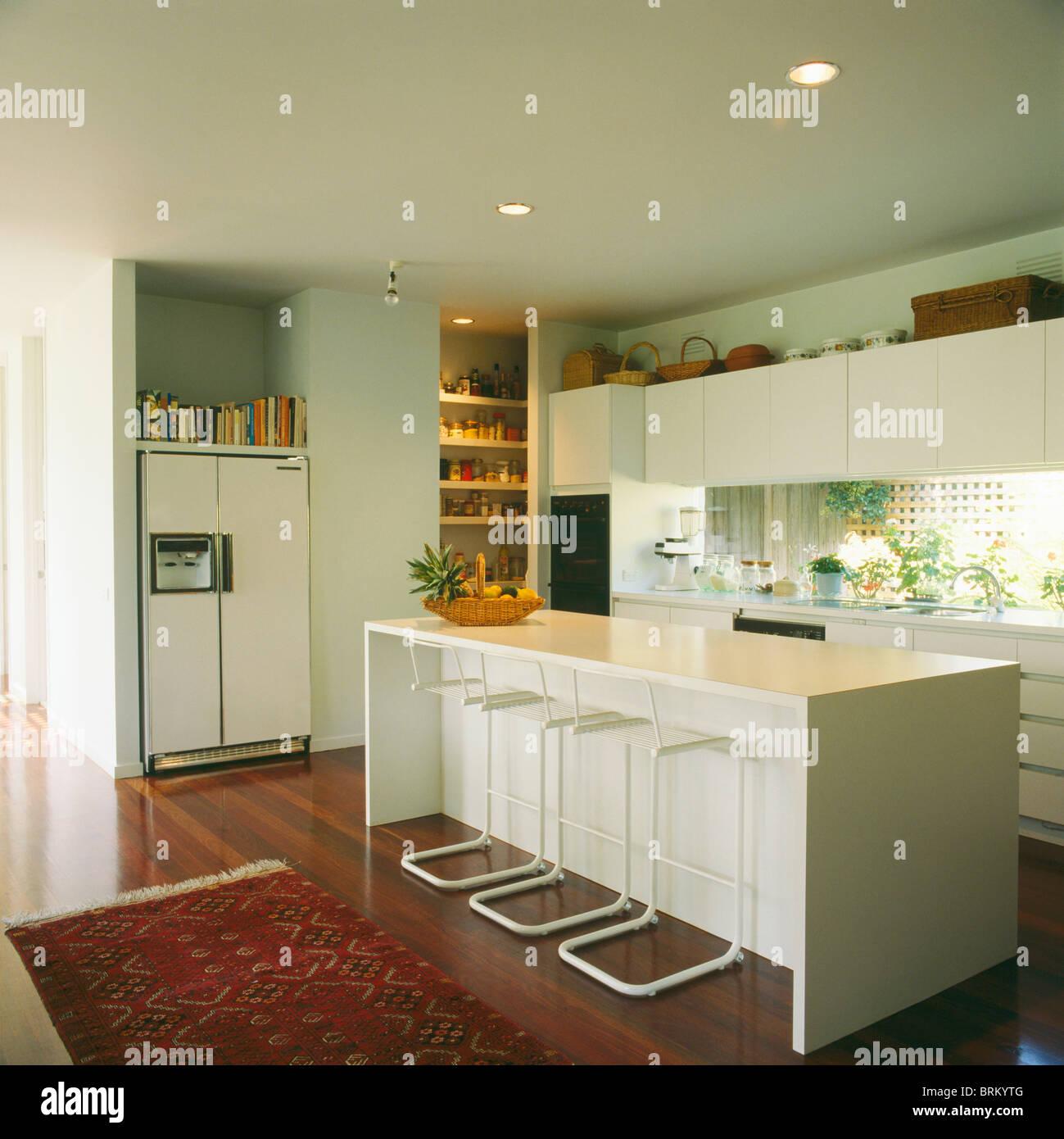 Fezes No Bar De Pequeno Branco Na Ilha Unidade Na Cozinha Moderna Em