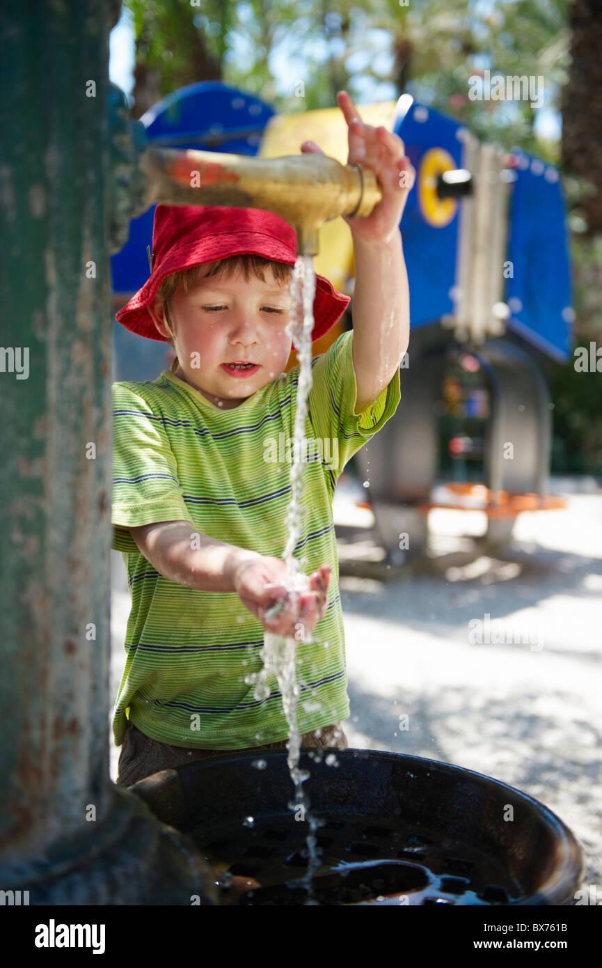 Rapaz lavar a sua mão em fonte de água fora no parque infantil Imagens de Stock