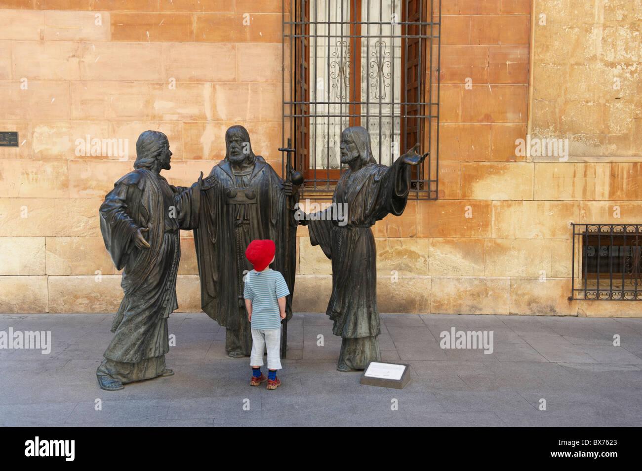 Rapaz a olhar em estátuas religiosas na histórica praça Imagens de Stock
