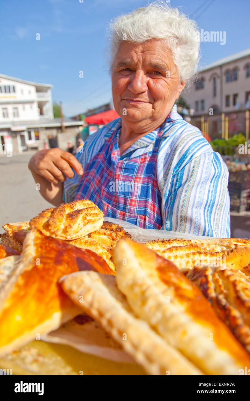 Mulher a venda de bolos no mercado ou um alimento Shuka em Vanadzor Arménia Imagens de Stock