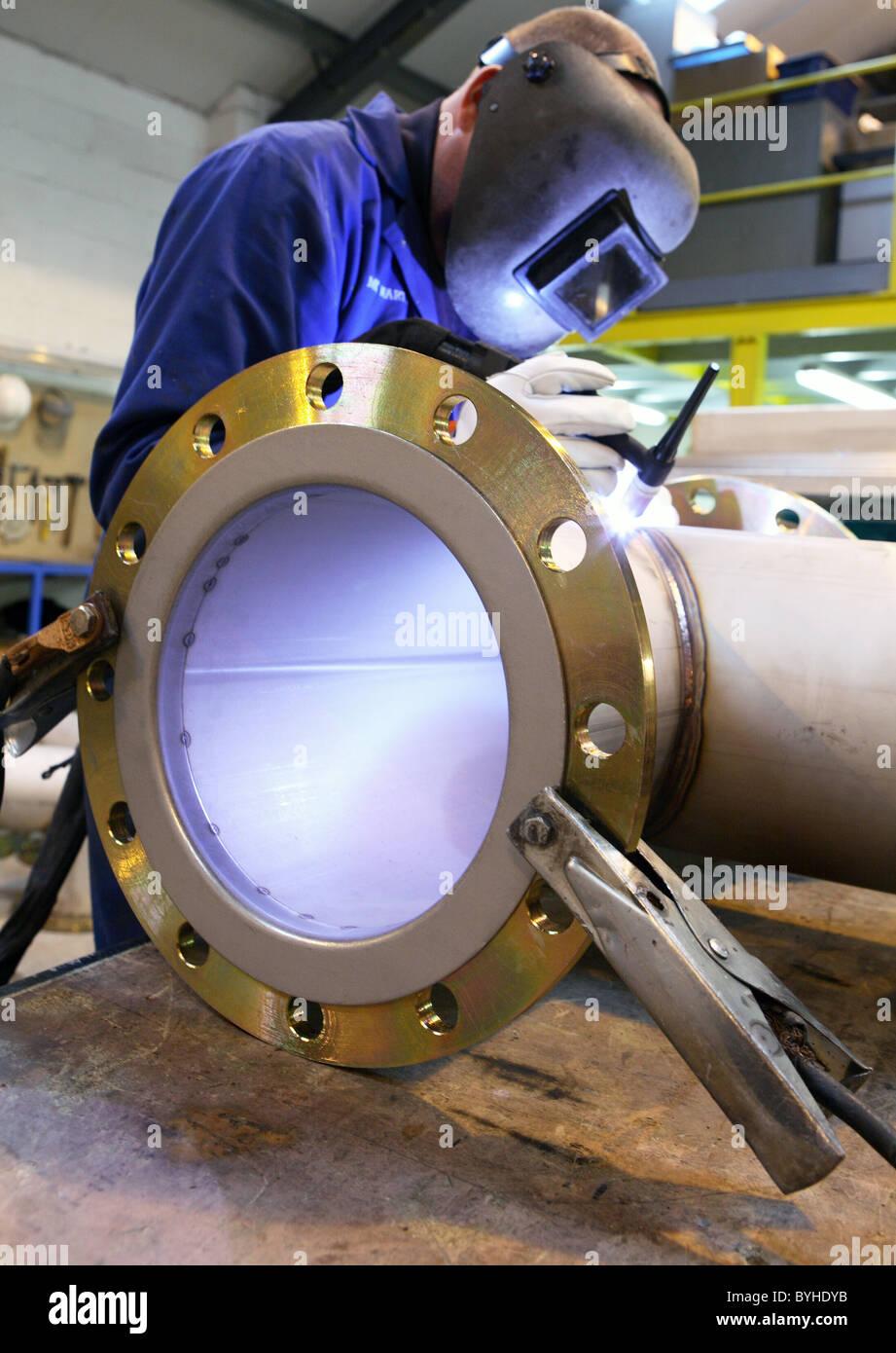 Soldador no trabalho em grandes de fabricação do tubo Imagens de Stock