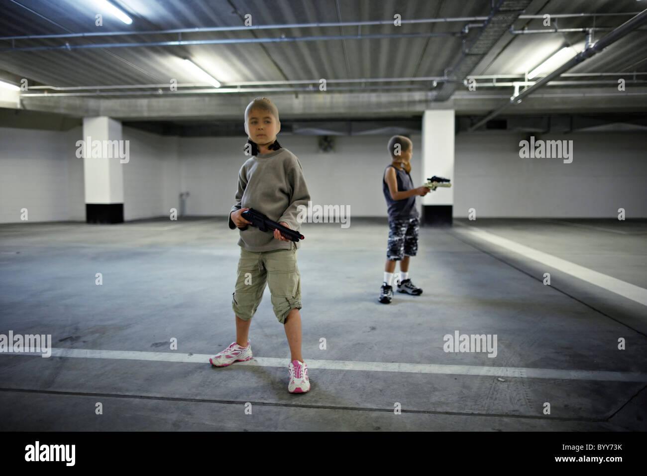 Crianças com factor de máscaras e armas de brinquedo no parque de estacionamento subterrâneo preparar Imagens de Stock