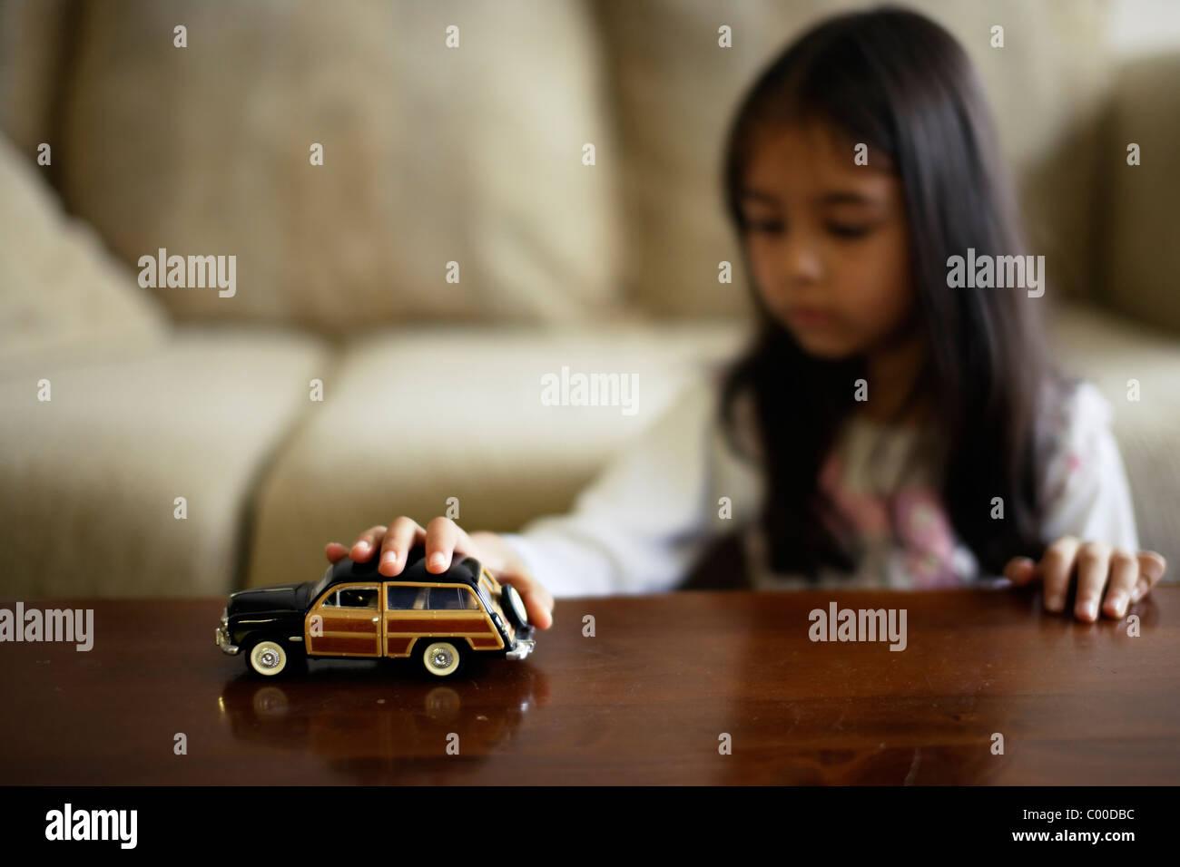 Menina brinca com brinquedos carros Imagens de Stock