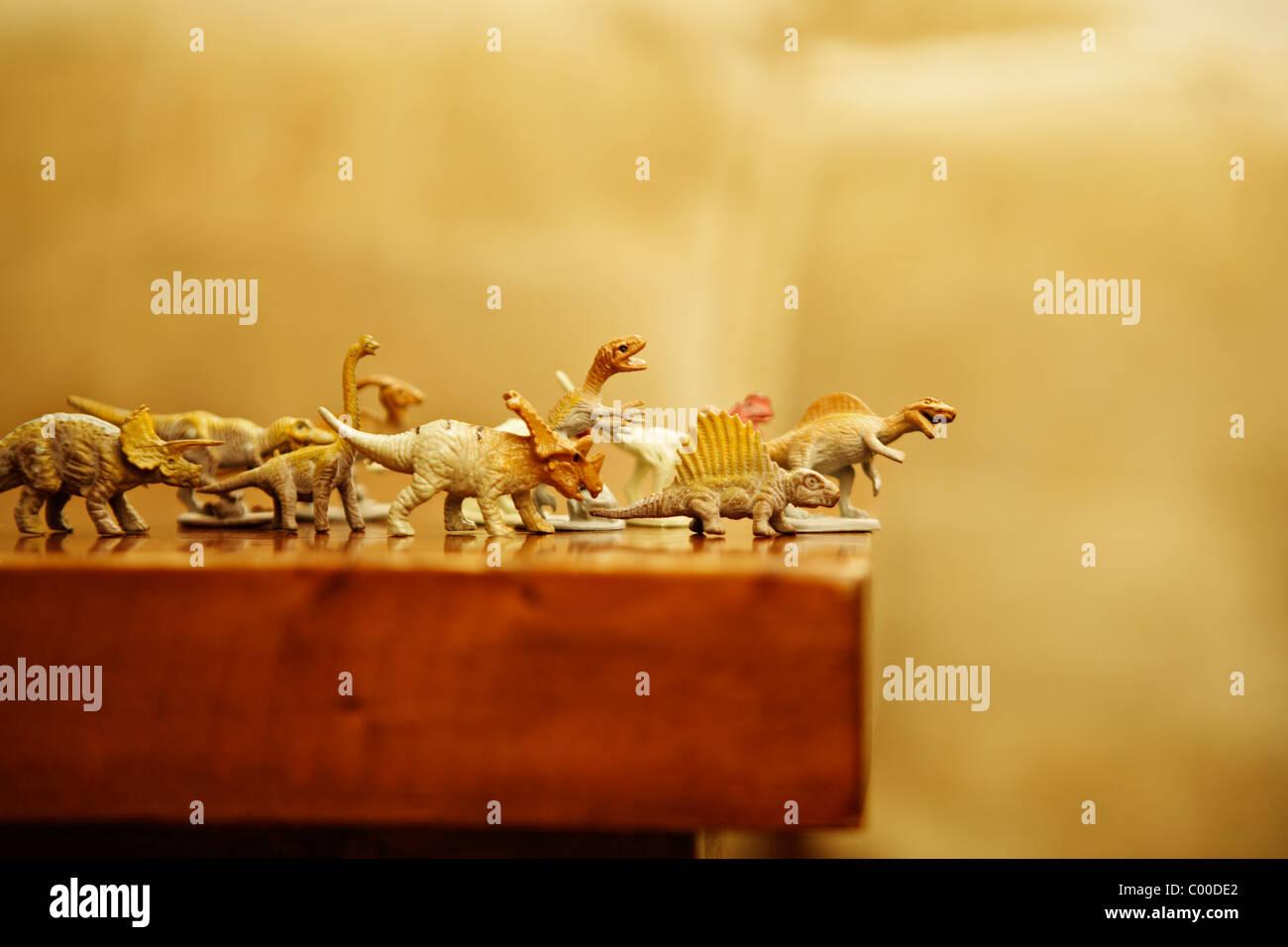 Dinossauros de brinquedo o rush da borda da tabela Imagens de Stock
