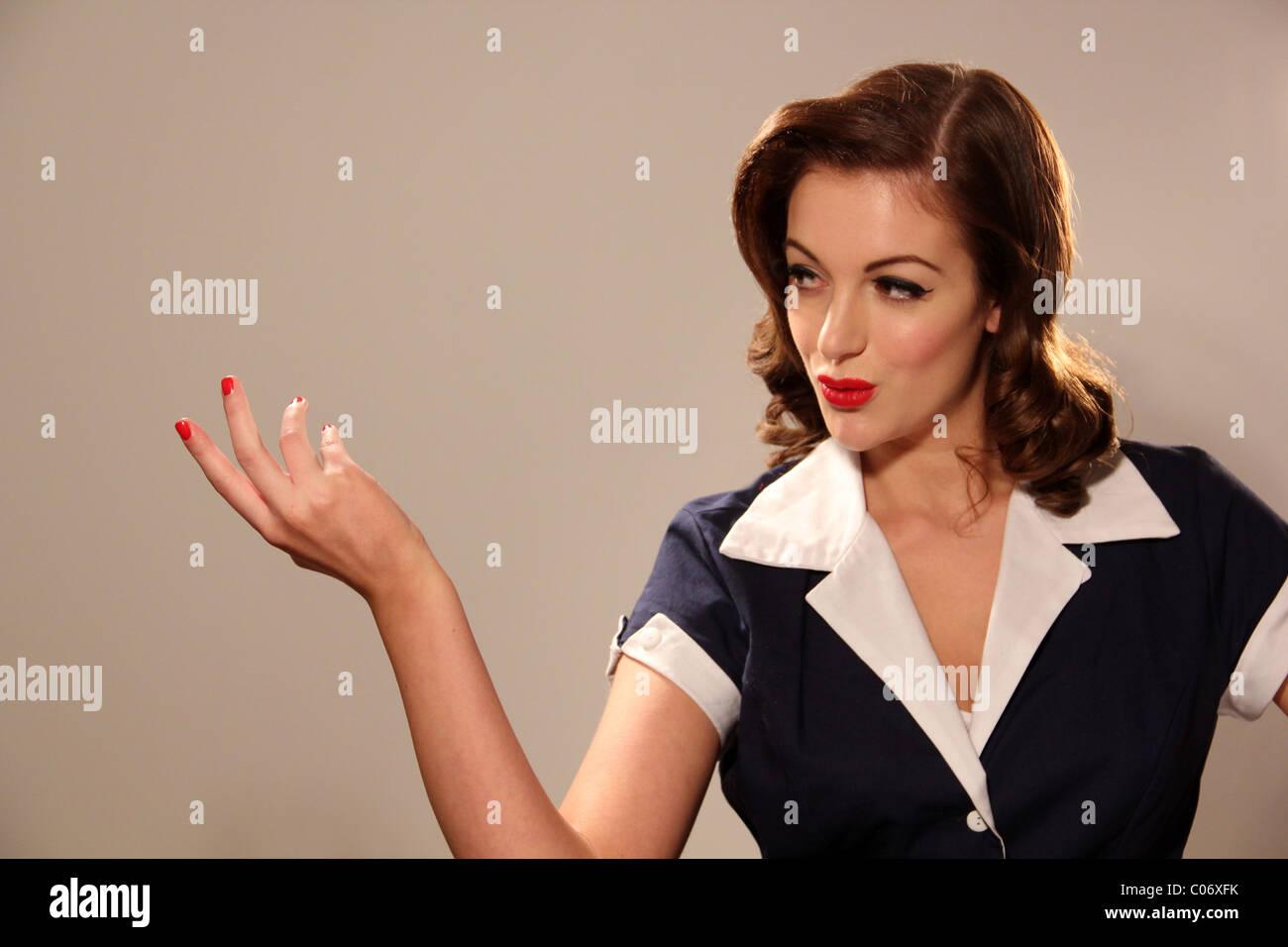 Mulher na década de vestuário apontando para um objeto imaginário Imagens de Stock