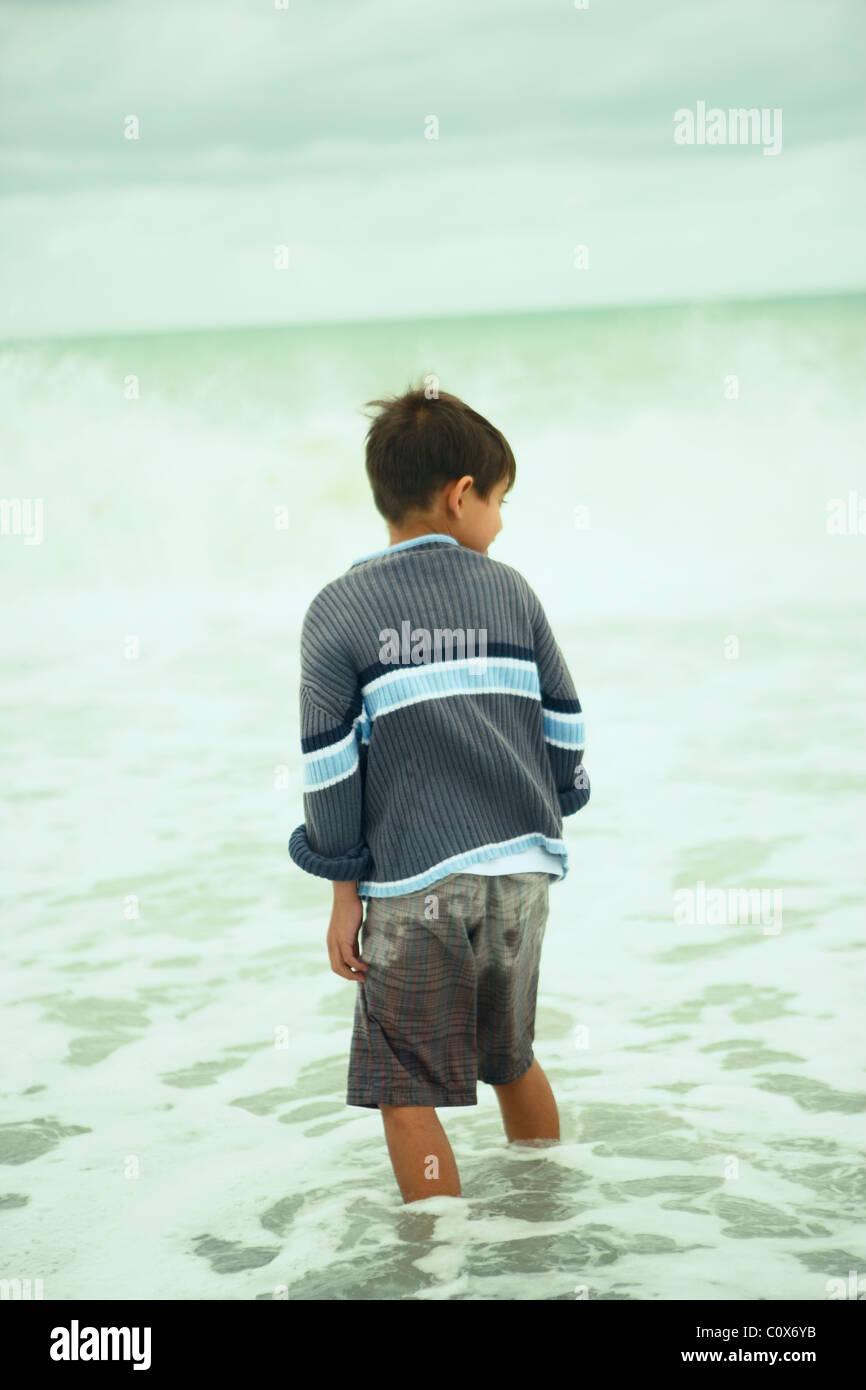 Menino de oito anos no mar em um dia nublado outonal, Napier, Nova Zelândia Imagens de Stock