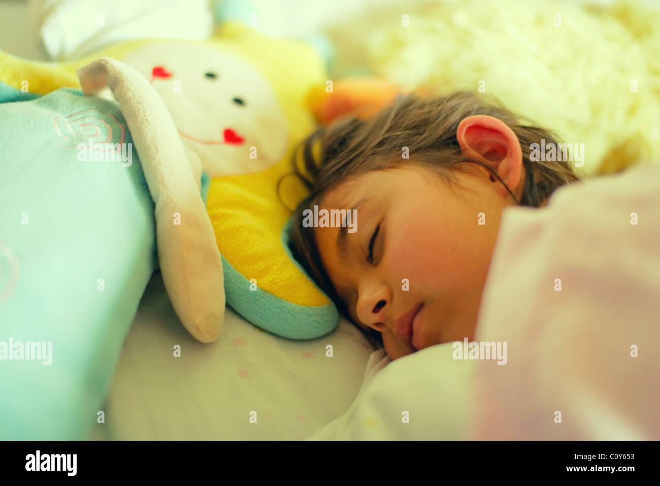 Rapariga tenha mentira com brinquedo doll na cama. Imagens de Stock