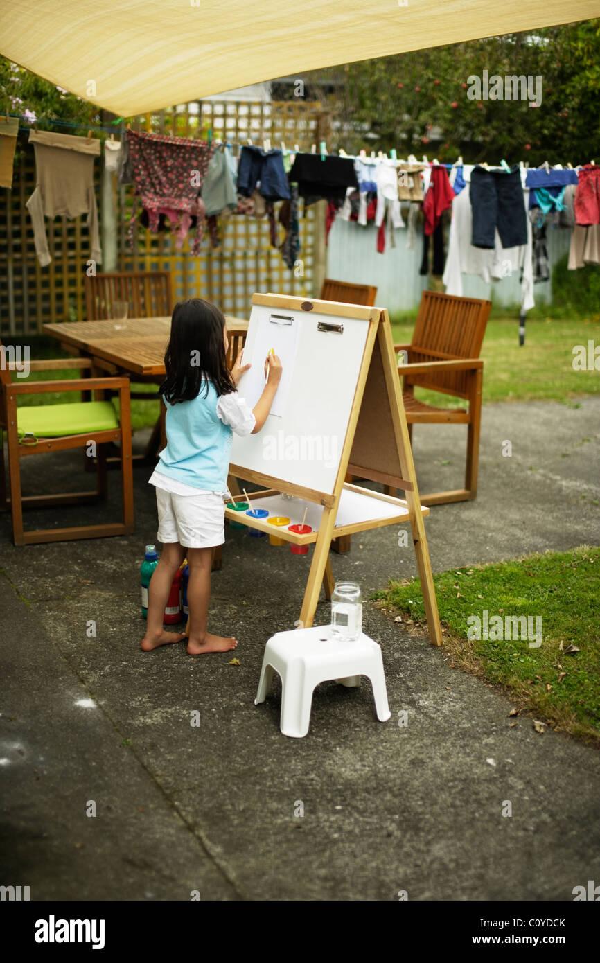 Menina pintura sobre o cavalete no quintal. Imagens de Stock