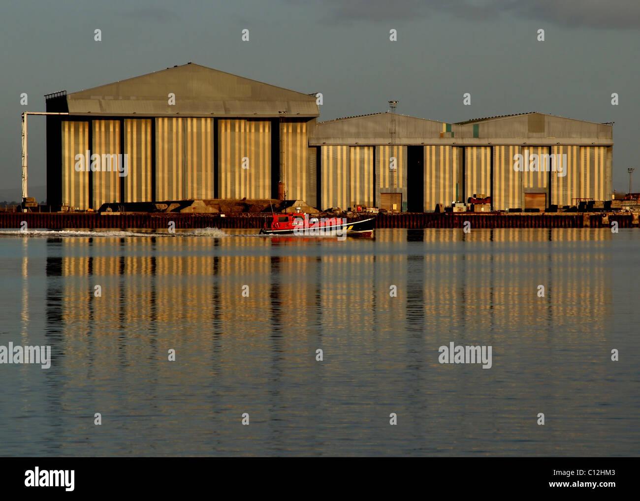 Um barco-piloto passa em frente da fabricação de metros, cujo Nigg galpões estão reflectidas Imagens de Stock