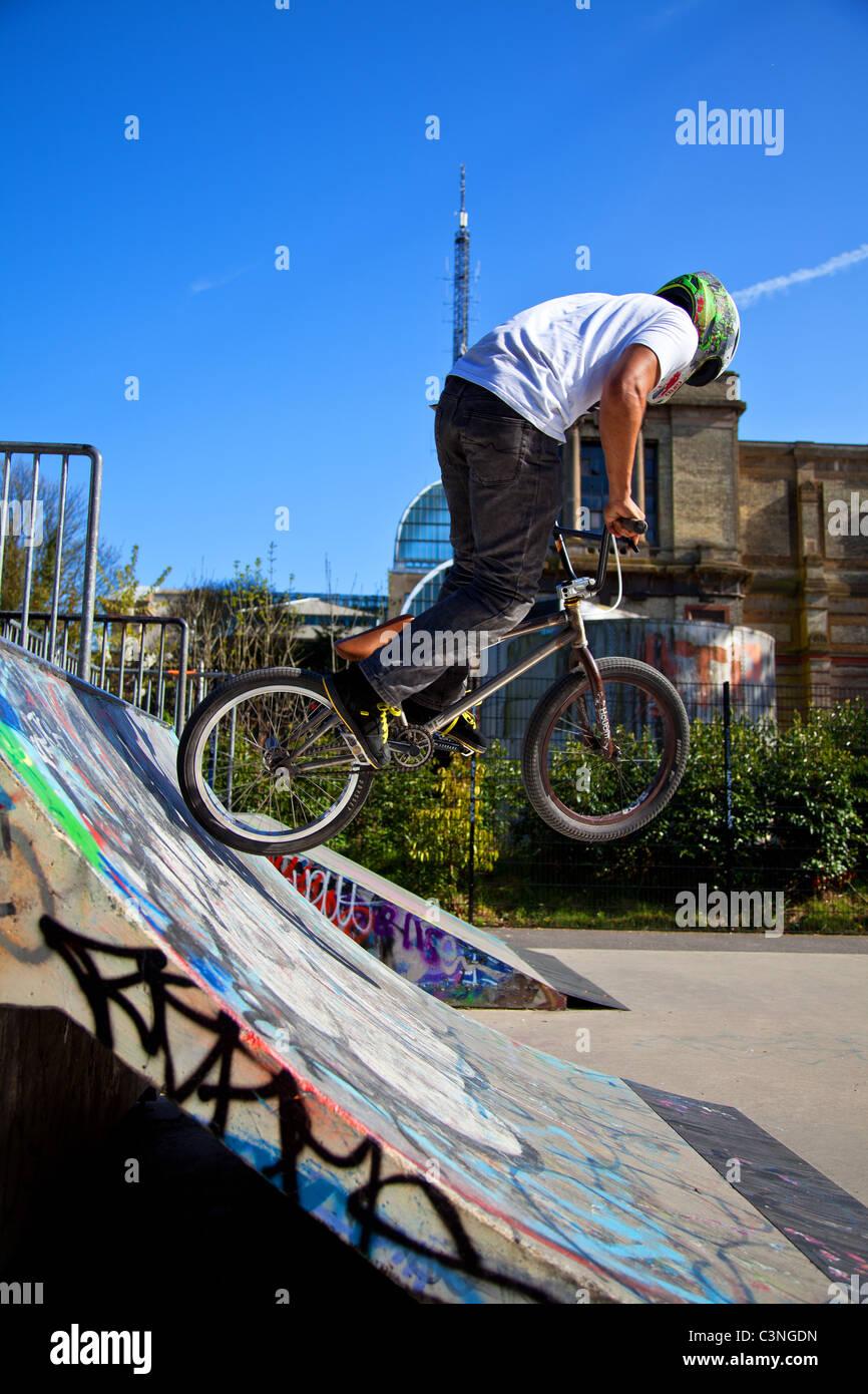 BMX biker realizando truques sobre uma rampa Imagens de Stock
