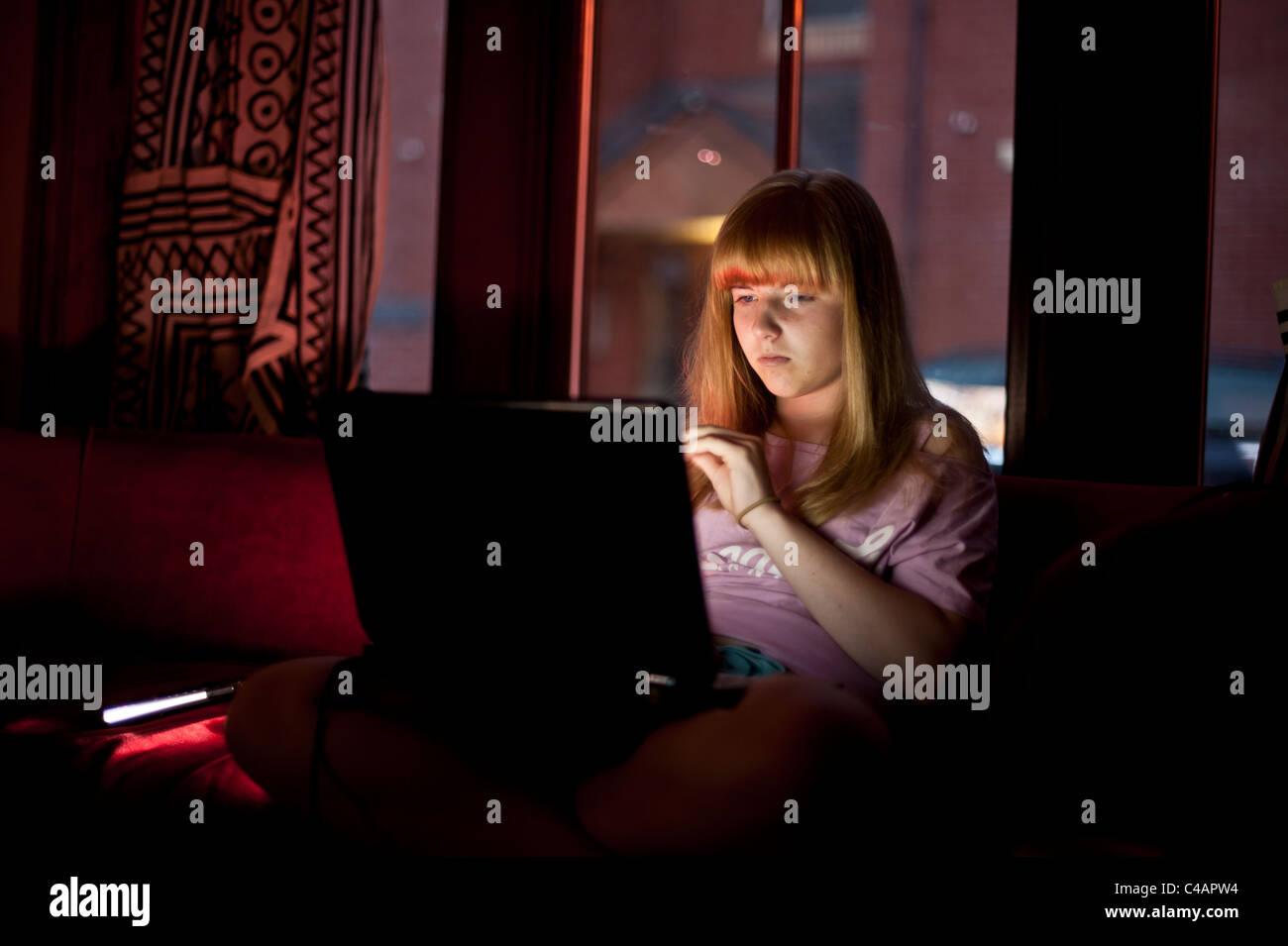 Uma adolescente verificar email a rede social FACEBOOK no seu computador portátil em casa à noite Reino Imagens de Stock