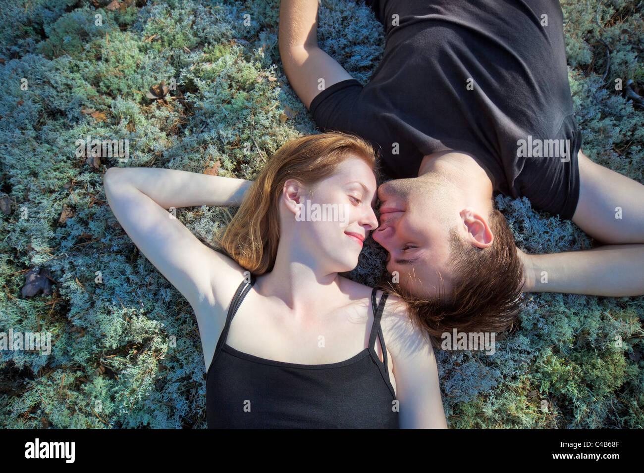 Jovem casal repousando sobre grama em floresta. Imagens de Stock