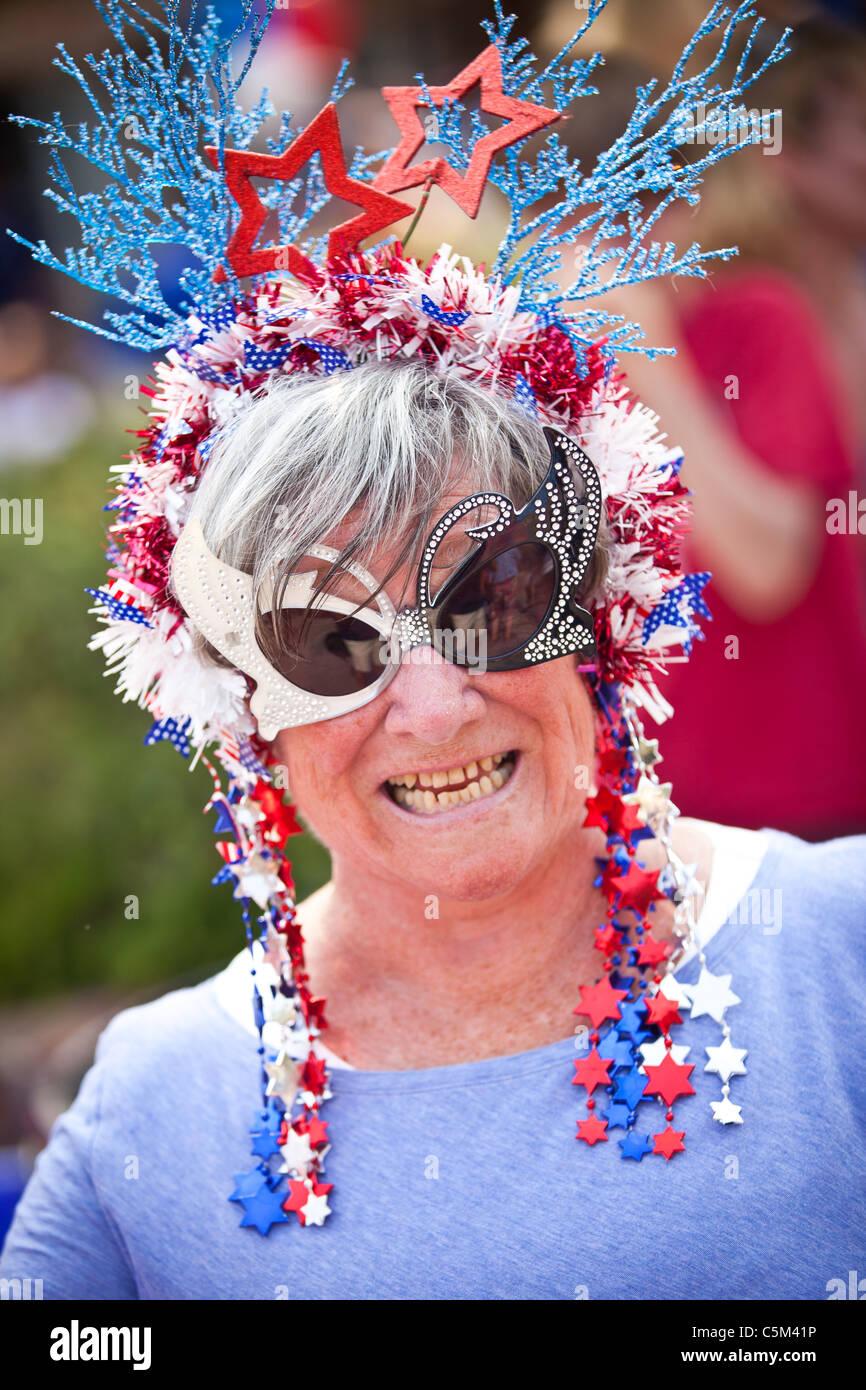 Uma mulher vestida em traje patriótico se destaca no I'na comunidade 4 de Julho desfile. Imagens de Stock