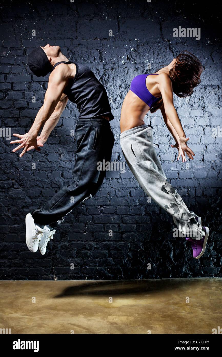 Jovem casal dançarino jumping. Na parede de fundo. Imagens de Stock